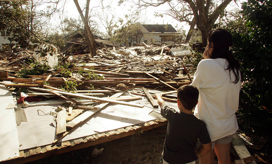 A woman reacts (R) as her son points to their demolished house by Hurricane Katrina in Gulfport, Mississippi August 30, 2005. © Frank Polich