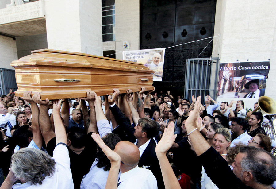 People carries the body of Vittorio Casamonica into a Roman Catholic basilica in a Rome suburb, where the funeral mass was celebrated, August 20, 2015. © Stringer