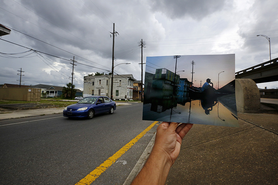 Photographer Carlos Barria holds a print of a photograph he took in 2005, as he matches it up at the same location 10 years on, in New Orleans, United States, August 18, 2015 © Carlos Barria