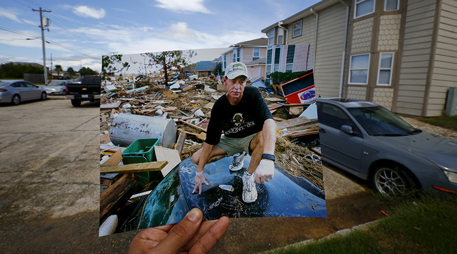 Photographer Carlos Barria holds a print of a photograph he took in 2005, as he matches it up at the same location 10 years on, in North Shore, northwest of New Orleans, United States, August 17, 2015 © Carlos Barria