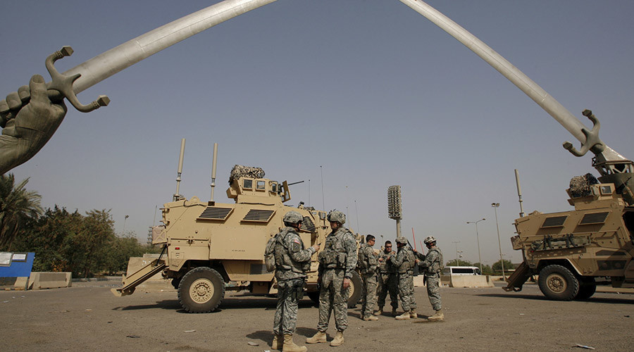 "U.S. soldiers wait before going out on a mission, under the ""Crossed-Sabers""-- a towering 160-tonne, bronze monument of two crossed swords held in Saddam's hands, at the fortified Green Zone in Baghdad. © Erik de Castro"