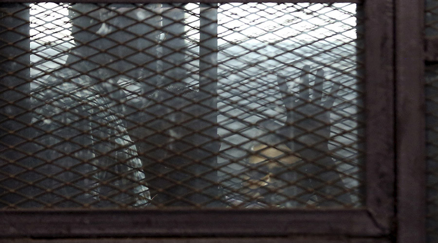 Al Jazeera television journalists Mohamed Fahmy and  Baher Mohamed are seen behind bars before hearing the verdict at a court in Cairo, Egypt, August 29, 2015. © Asmaa Waguih