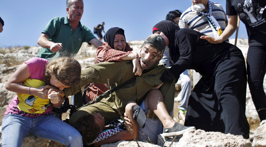 Palestinians scuffle with an Israeli soldier as they try to prevent him from detaining a boy during a protest against Jewish settlements in the West Bank village of Nabi Saleh, near Ramallah August 28, 2015. © Mohamad Torokman