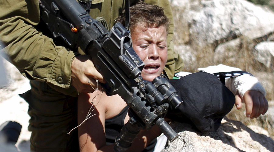An Israeli soldier detains a Palestinian boy during a protest against Jewish settlements in the West Bank village of Nabi Saleh, near Ramallah August 28, 2015. © Mohamad Torokman