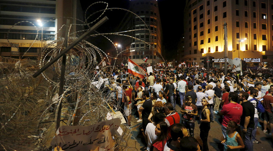 Protesters carry banners and Lebanese national flags as they stand near barbed wire erected near the government palace in downtown Beirut, Lebanon August 29, 2015 © Jamal Saidi