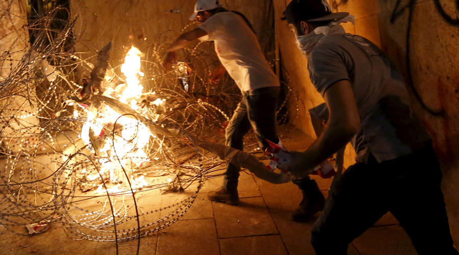 Protesters set trash on fire on barbed wire erected near the government palace in downtown Beirut, Lebanon August 29, 2015. © Jamal Saidi