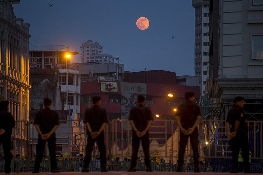The moon rises as police officers stand guard near Central Market in Malaysia's capital city of Kuala Lumpur, August 29, 2015. © Athit Perawongmetha