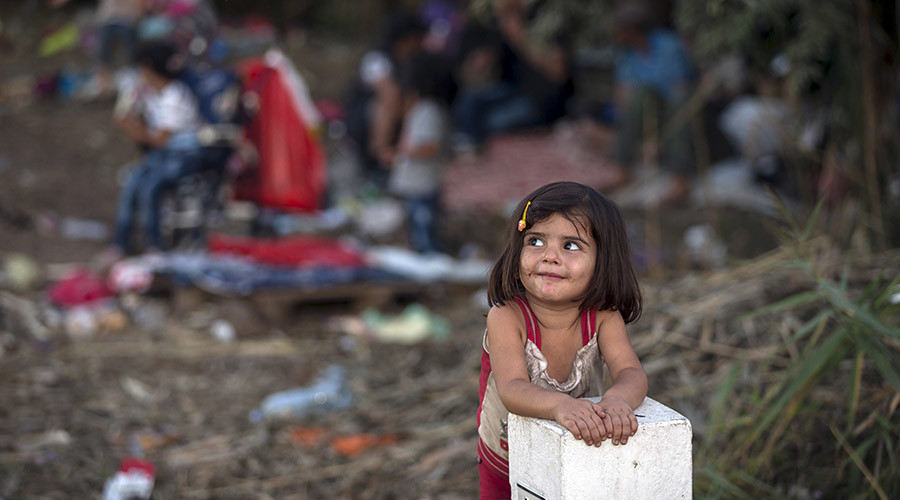 A Syrian migrant girl leans on a border stone on the Serbian border with Hungary near the village of Horgos August 27, 2015. © Marko Djurica