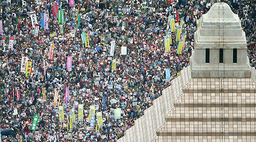 People hold placards and shout slogans as they gather to protest against Japan's Prime Minister Shinzo Abe's security bill outside the parliament in Tokyo, in this photo taken by Kyodo August 30, 2015 © Kyodo