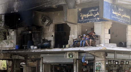 Residents sit on a couch on a balcony of a damaged building in Aleppo's al-Shaar neighboirhood, Syria, August 1, 2015. © Abdalrhman Ismail