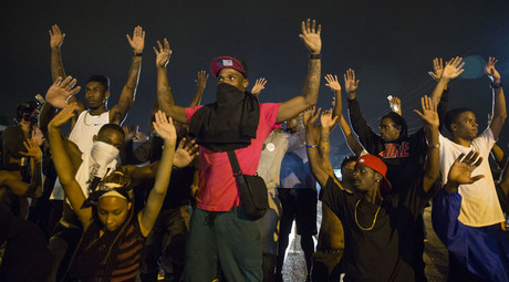 Demonstrators confront police with their arms raised during on-going demonstrations to protest against the shooting of Michael Brown, in Ferguson, Missouri, August 16, 2014. © Lucas Jackson