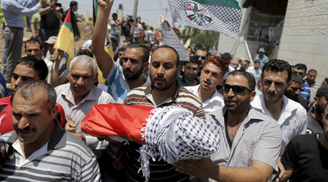 A mourner carries the body of 18-month-old Palestinian baby Ali Dawabsheh, who was killed after his family's house was set to fire in a suspected attack by Jewish extremists in Duma village near the West Bank city of Nablus July 31, 2015. © Ammar Awad