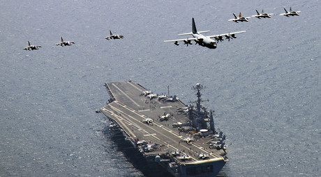 A U.S. Marine Corps C-130 Hercules aircraft leads a formation of F/A-18C Hornet strike fighters and A/V-8B Harrier jets over the aircraft carrier USS George Washington (CVN 73) in the East Sea of Korea © Charles Oki / U.S. Navy photo / Handout