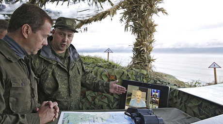 Russia's Prime Minister Dmitry Medvedev (L) inspects a machine gun regiment during his visit to Iturup Island, one of four islands known as the Southern Kurils in Russia and Northern Territories in Japan, August 22, 2015 © Dmitry Astakhov