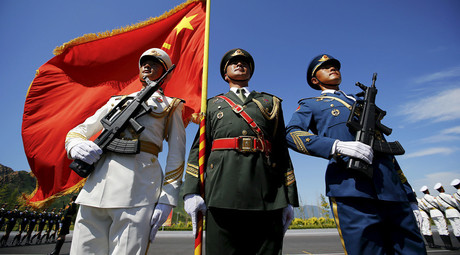 Officers and soldiers of China's People's Liberation Army hold a flag and weapons during a training session for a military parade to mark the 70th anniversary of the end of the World War Two, at a military base in Beijing, China, August 22, 2015. © Damir Sagolj