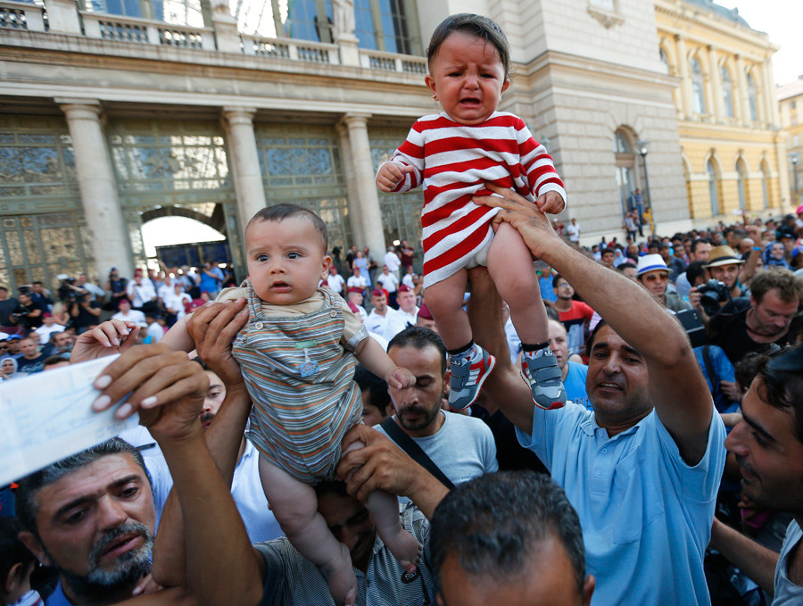 Migrants wave their train tickets and lift up children outside the main Eastern Railway station in Budapest, Hungary, September 1, 2015. © Laszlo Balogh