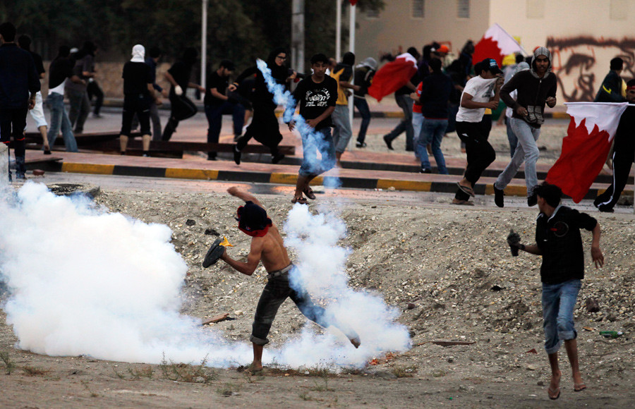 An anti-government protester throws a tear gas canister back to riot-police during clashes in the village of Aali, south of Manama November 26, 2011. © Hamad I Mohammed