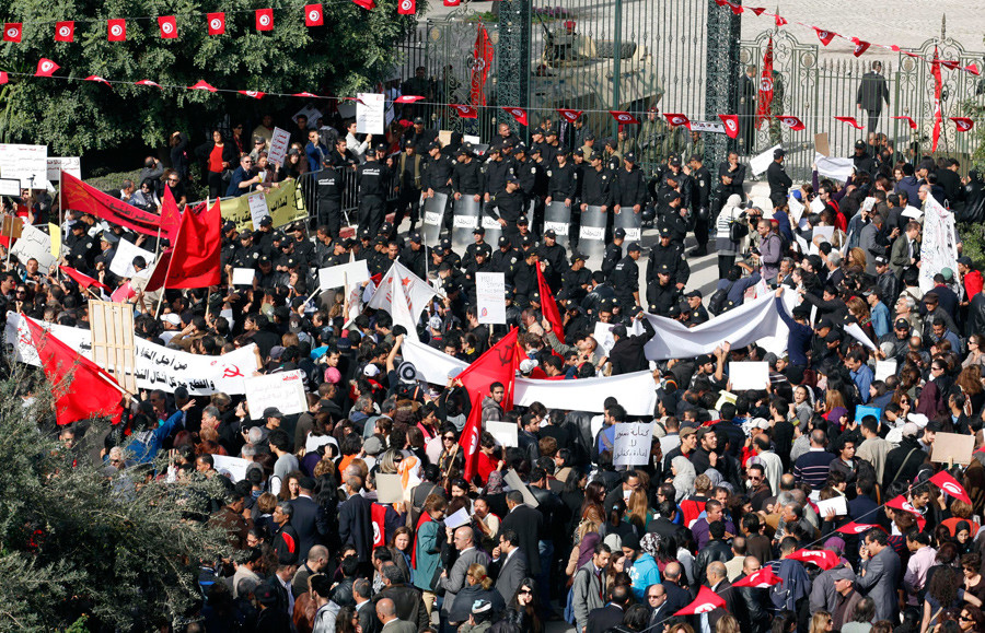 Protesters stand in front of riot police during a demonstration outside the parliamentary building in Tunis November 22, 2011. © Zoubeir Souissi