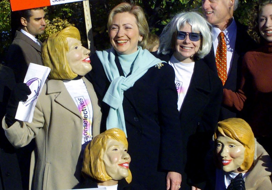 Hillary Clinton poses with women in Hillary Clinton masks while campaigning for Senate in 2000.