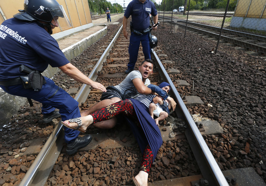 Hungarian policemen stand by the family of migrants as they wanted to run away at the railway station in the town of Bicske, Hungary, September 3, 2015. © Laszlo Balogh