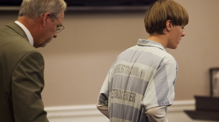 Dylann Roof (R), the 21-year-old man charged with murdering nine worshippers at a historic black church in Charleston last month, is helped to his chair by chief public defender Ashley Pennington during a hearing at the Judicial Center in Charleston, South Carolina July 16, 2015. © Randall Hill