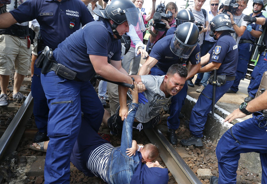 Hungarian policemen detain migrants on the tracks as they wanted to run away at the railway station in the town of Bicske, Hungary, September 3, 2015. © Laszlo Balogh