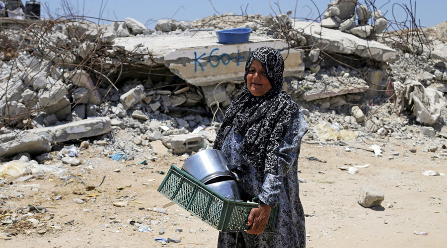 A Palestinian woman walks past the remains of a house, that witnesses said was destroyed by Israeli shelling during a 50-day war last summer, in Khan Younis in the southern Gaza Strip. © Ibraheem Abu Mustafa