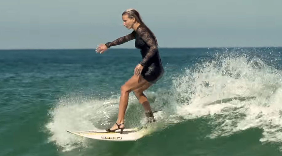 Cowabunga! French surfer rides waves in high heels & cocktail dress (VIDEO)