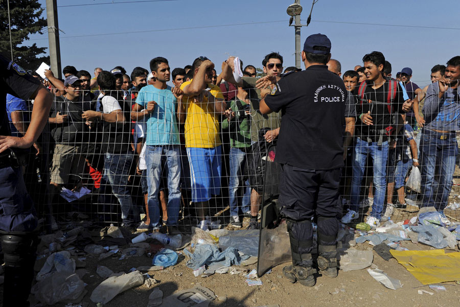 A Greek police officer stands guard as refugees and migrants wait to cross the borders of Greece with Macedonia, near the village of Idomeni September 4, 2015. © Alexandros Avramidis