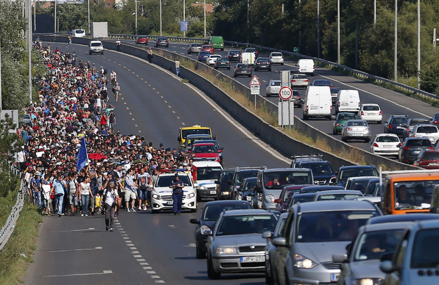 Migrants march along the highway for the border with Austria, out of Budapest, Hungary, September 4, 2015. © Laszlo Balogh