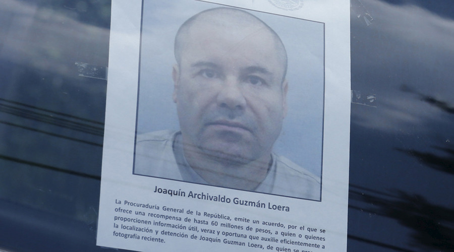 "A police vehicle is seen a poster with a photo of drug lord Joaquin ""El Chapo"" Guzman © Henry Romero"