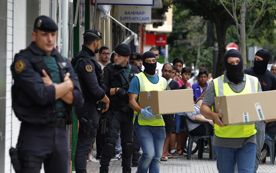 Spanish police carry boxes of evidences as they leave the house of an 18-year-old Moroccan woman suspected of recruiting other women via the Internet to the jihadist group Islamic State (IS), in Gandia on September 5, 2015. © Jose Jordan