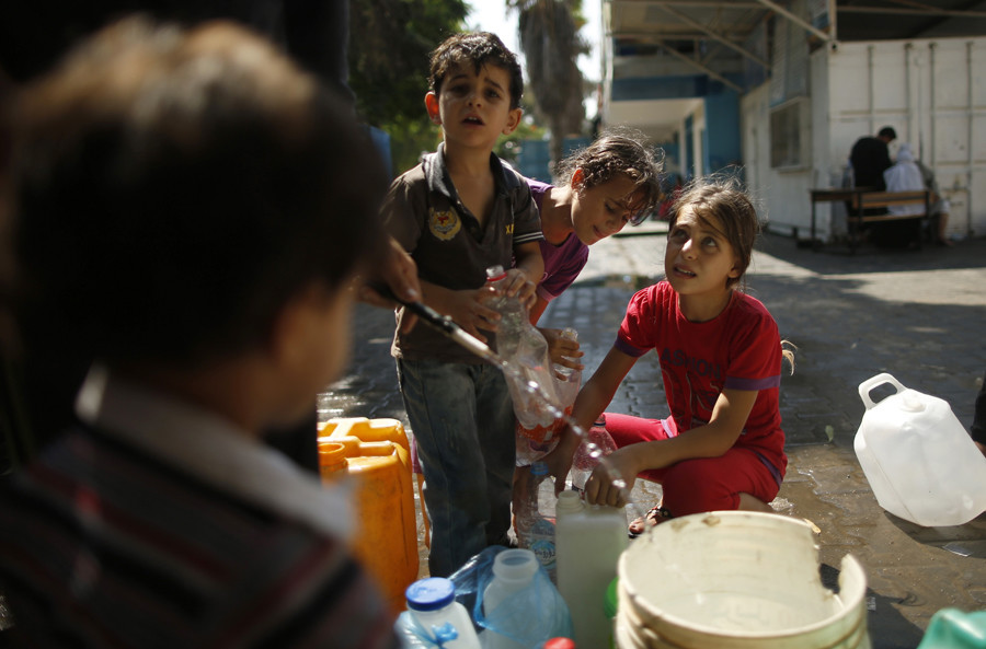 Palestinian children, who fled their houses during an Israeli offensive, fill bottles with water at a United Nations-run school, sheltering displaced Palestinians, in Gaza City © Mohammed Salem
