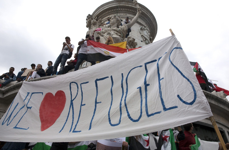 "People hold a banner that says ""We love refugees"" as they take part in a demonstration asking for a change in the refugee policy in Europe on the Republique square in Paris, France, September 5, 2015. © Philippe Wojazer"