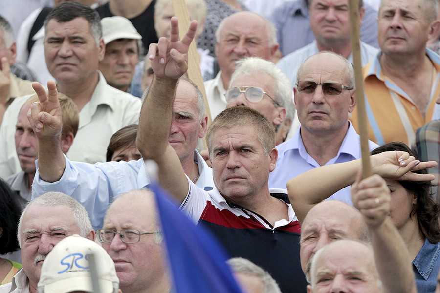 """Protesters gesture during an anti-government rally, organised by the civic platform """"Dignity and Truth"""" (DA), in central Chisinau, Moldova, September 6, 2015. © Valery Korchmar"""