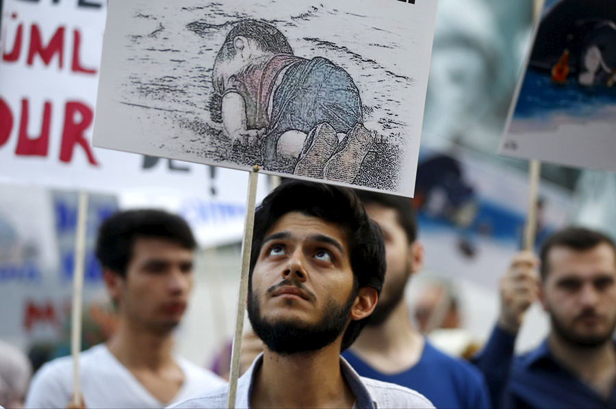 A man holds a poster with a drawing depicting a drowned Syrian toddler during a demonstration for refugee rights in Istanbul, Turkey, September 3, 2015. © Osman Orsal