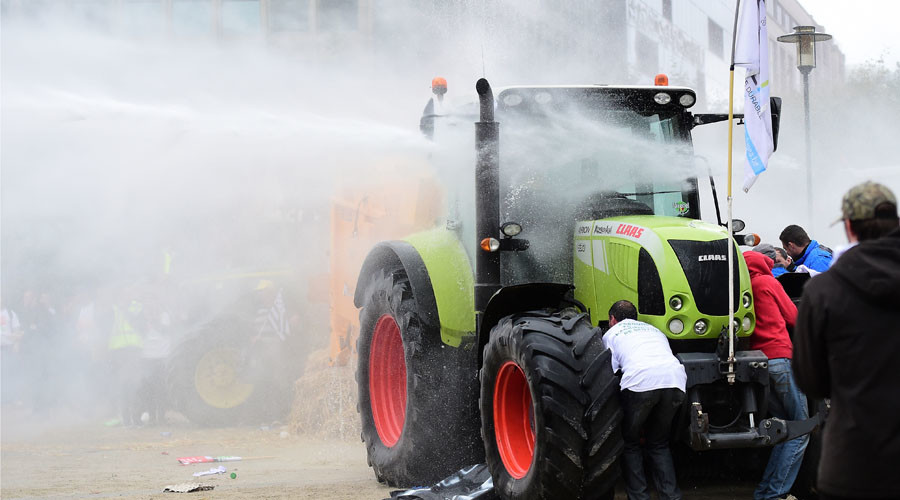 Protestors take cover behind a tractor from a water canon during a farmers demonstration in front of the European Commission building on September 7, 2015, in Brussels, as European agriculture ministers hold an extraordinary meeting at the European Council. © Emmanuel Dunand