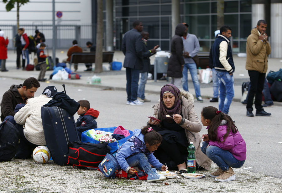 Migrants eat outside a makeshift refugee camp at the fair ground of Munich, Germany September 7, 2015. © Michaela Rehle