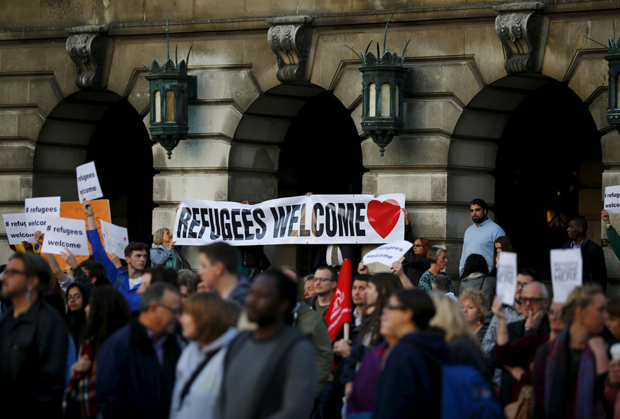 People hold up banners during a vigil for refugees in Nottingham, Britain, September 7, 2015. © Reuters
