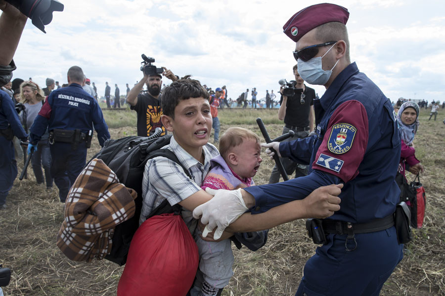 A migrant carrying a baby is stopped by Hungarian police officers as he tries to escape on a field nearby a collection point in the village of Roszke, Hungary, September 8, 2015. © Reuters