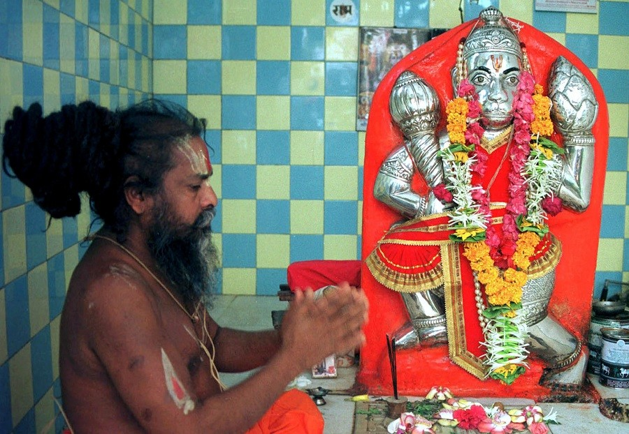 A priest worships before Hindu god Hanuman