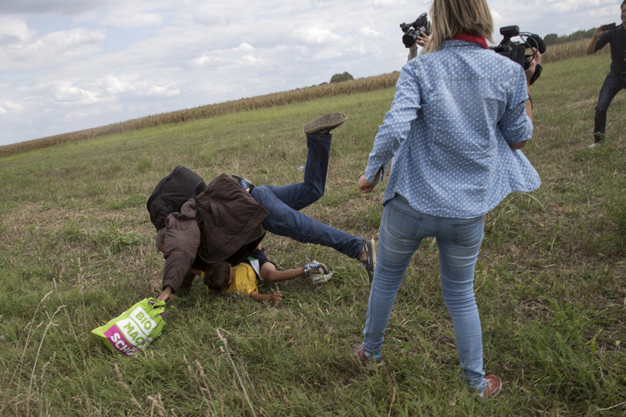 A migrant carrying a child falls after tripping on a TV camerawoman (R) while trying to escape from a collection point in Roszke village, Hungary, September 8, 2015. © Marko Djurica