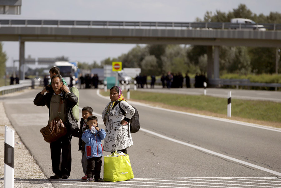 Migrants stand on the M5 highway  after leaving a collection point in the village of Roszke, Hungary September 9, 2015. © Marko Djurica