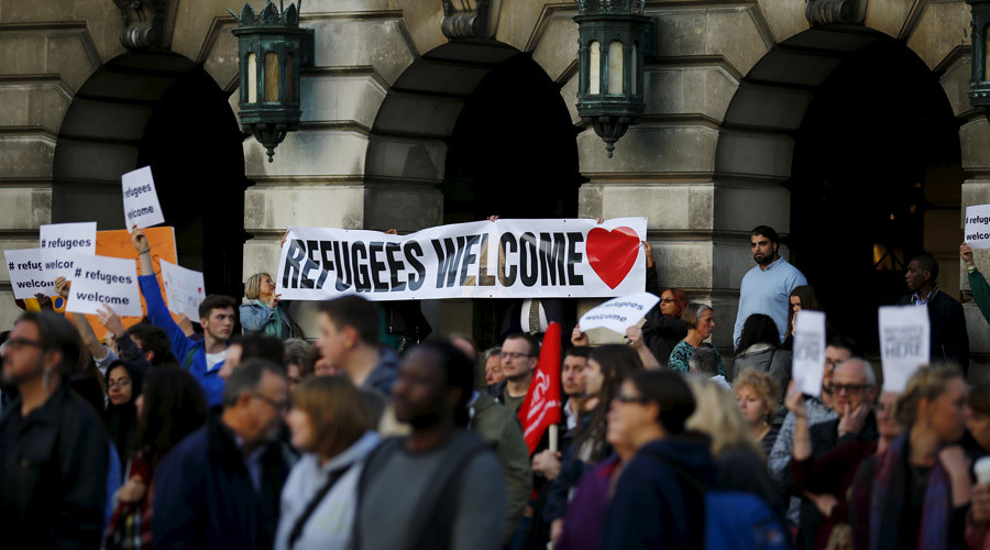 People hold up banners during a vigil for refugees in Nottingham, Britain, September 7, 2015. © Darren Staples