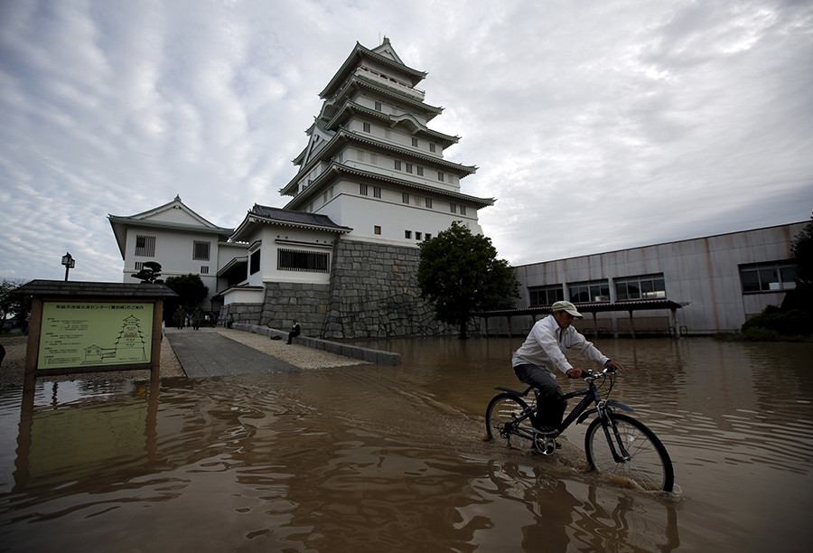 A local resident riding a bicycle goes through a residential area flooded by the Kinugawa river, caused by typhoon Etau, in front of the castle-shaped Joso City local interchange center in Joso, Ibaraki prefecture, Japan, September 11, 2015 © Issei Kato