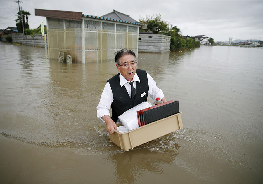 A man holding a tray of belongings wades through a road at an area flooded by the Omoigawa river, caused by typhoon Etau in Oyama, Tochigi prefecture, Japan © Kyodo