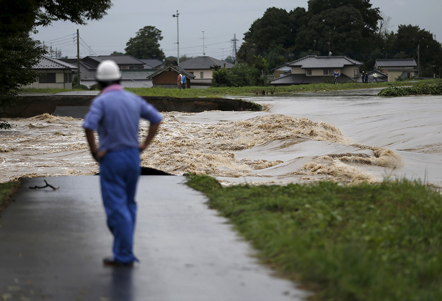 A man looks at floodwaters at a break in the dike of the Kinugawa river (R) at a residential area flooded by the river, caused by typhoon Etau in Joso, Ibaraki prefecture, Japan, September 10, 2015 © Issei Kato