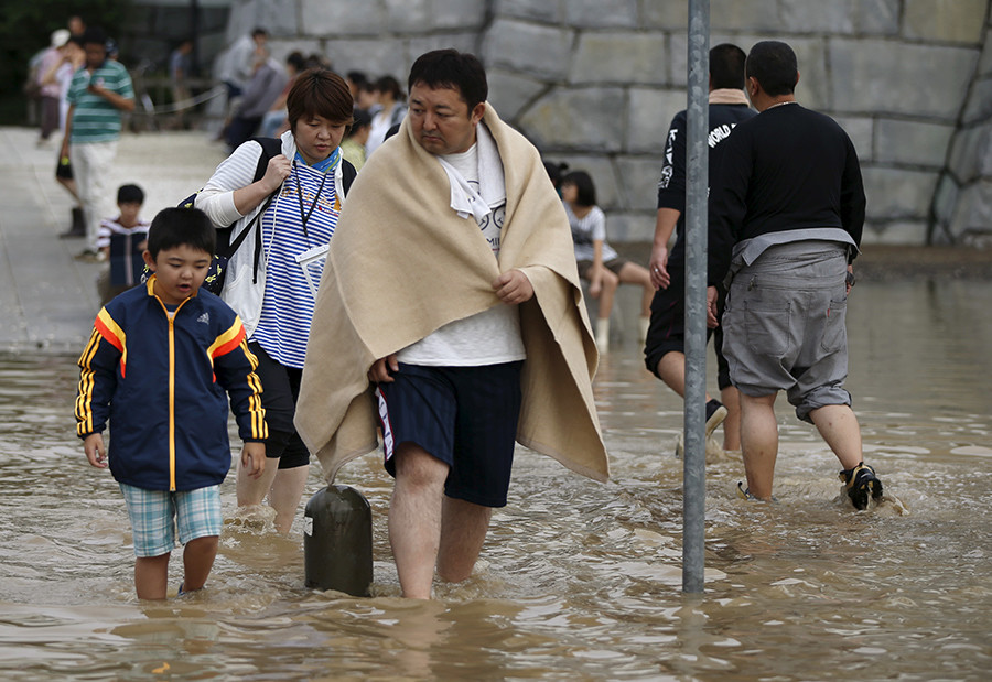 Local residents wade through a residential area flooded by the Kinugawa river, caused by typhoon Etau, in Joso, Ibaraki prefecture, Japan, September 11, 2015 © Issei Kato