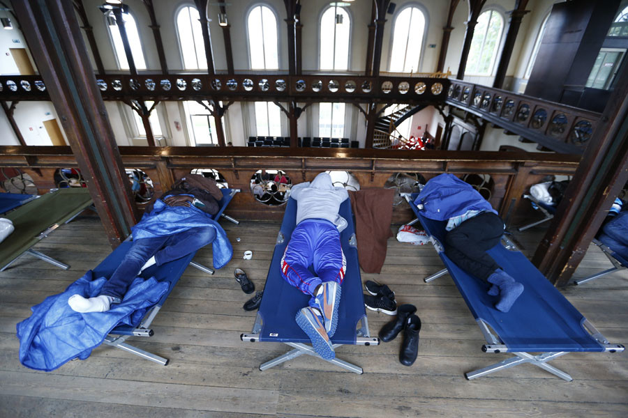 Migrants rest on a camp-beds at the City Hall in Rottenburg, Germany September 7, 2015. © Ralph Orlowski