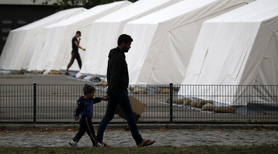 Migrants walk past tents inside a refugee camp at a former police compound in Berlin, Germany September 7, 2015. © Fabrizio Bensch
